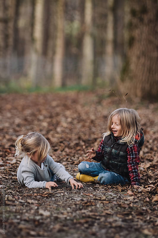 little boy and girl having fun in autumnal forest by Leander Nardin for Stocksy United