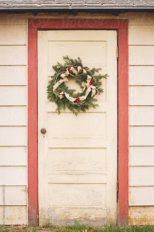 The door of an old shed decorated with a wreath for the holidays by Tana Teel for Stocksy United