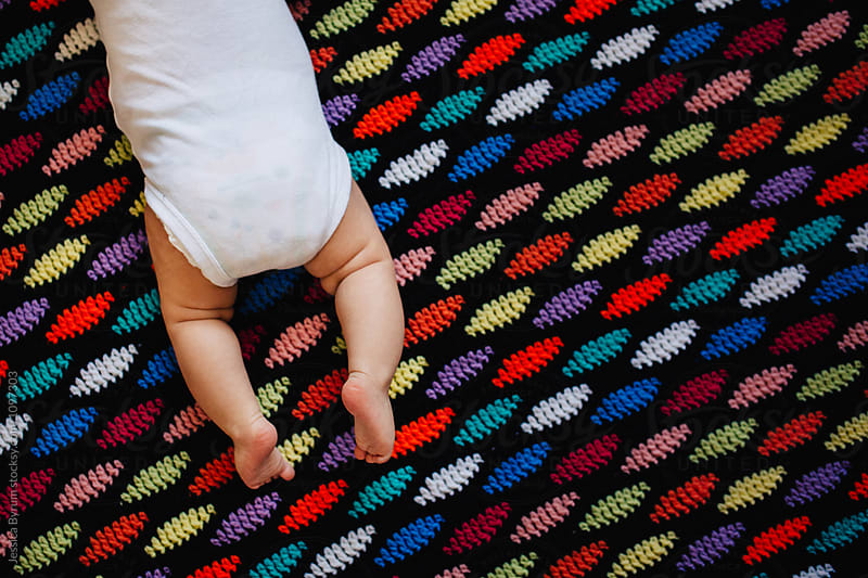 3 month old baby lying on a colorful homemade afghan blanket. by Jessica Byrum for Stocksy United