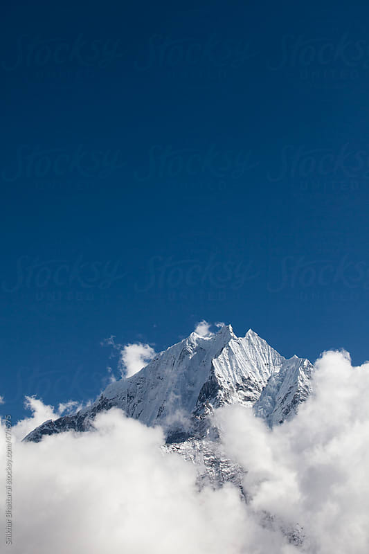 Mt. Thamserku in the everest region peeking through the clouds. by Shikhar Bhattarai for Stocksy United