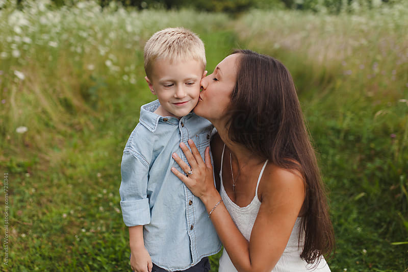 A mom kisses her son on the cheek by Amanda Worrall for Stocksy United