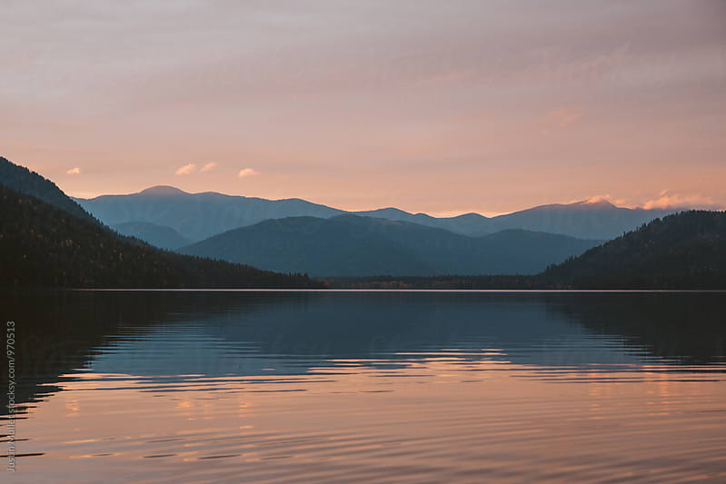 Sunset hues over a still lake by Justin Mullet for Stocksy United
