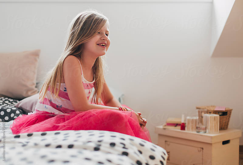 Smiling Girl Sitting on Bed by Lumina for Stocksy United
