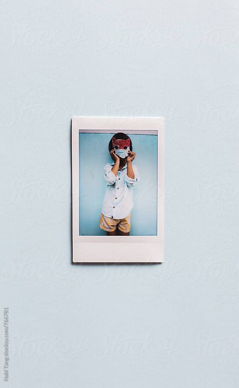 Polaroid portrait of a boy playing with his handmade paper mask by Nabi Tang for Stocksy United