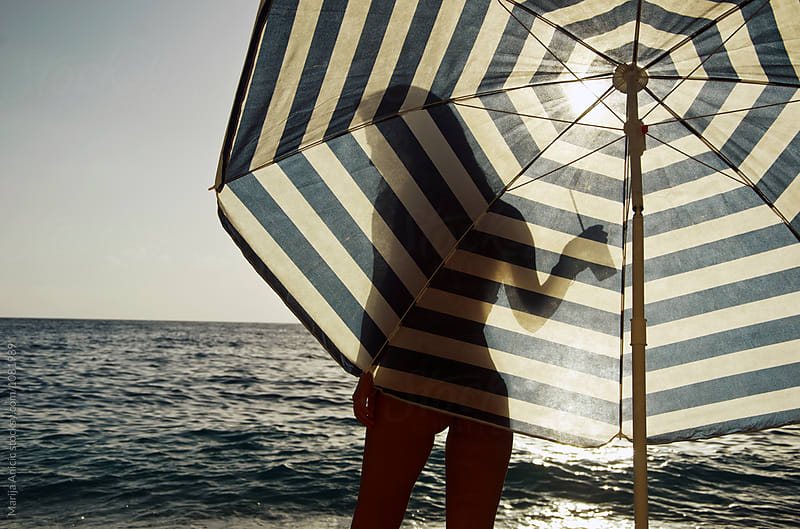 Hansome sillouette in front of the umbrella  by Marija Anicic for Stocksy United