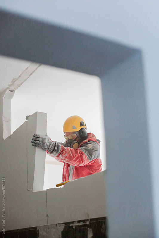Construction worker demolishes interior wall by Jelena Jojic Tomic for Stocksy United