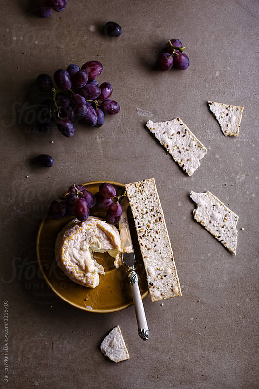 Langres cheese with grapes and crackers. by Darren Muir for Stocksy United
