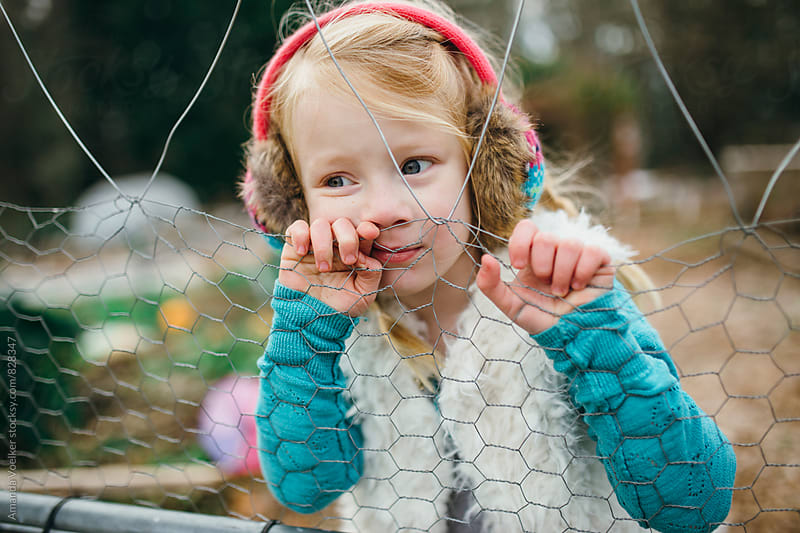 Little Girl Presses Her face against a wire Fence by Amanda Voelker for Stocksy United