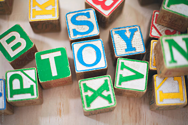 close up of a child's wooden alphabet blocks spelling toy by Natalie JEFFCOTT for Stocksy United