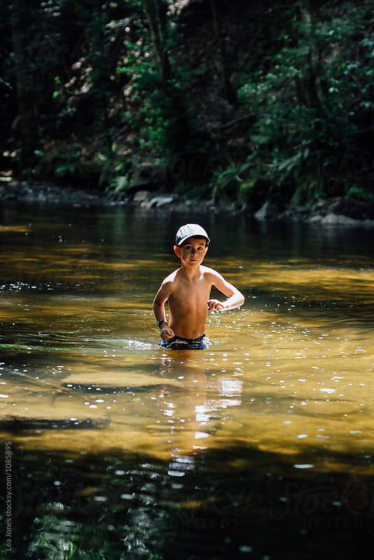 boy playing in a river by Léa Jones for Stocksy United