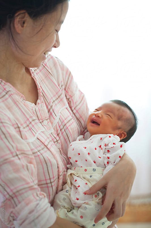 young asian mother holding her newborn baby smile by Bo Bo for Stocksy United