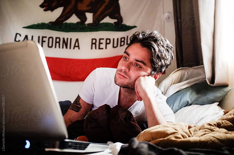 A man using a laptop on his bed with the california flag in background by J Danielle Wehunt for Stocksy United