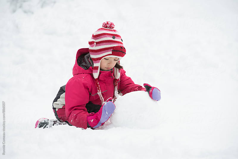Little Girl Making A Snowman by Ronnie Comeau for Stocksy United