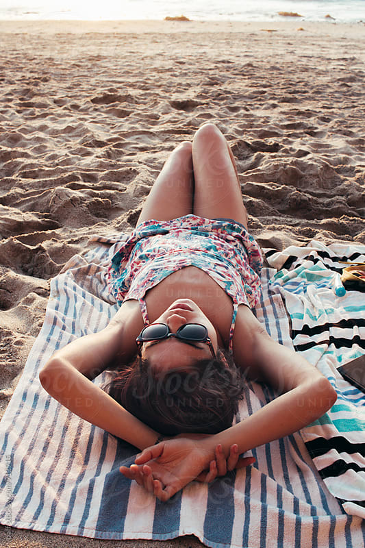 Young Thai woman relaxing on her towel at the beach in a dress by paff for Stocksy United