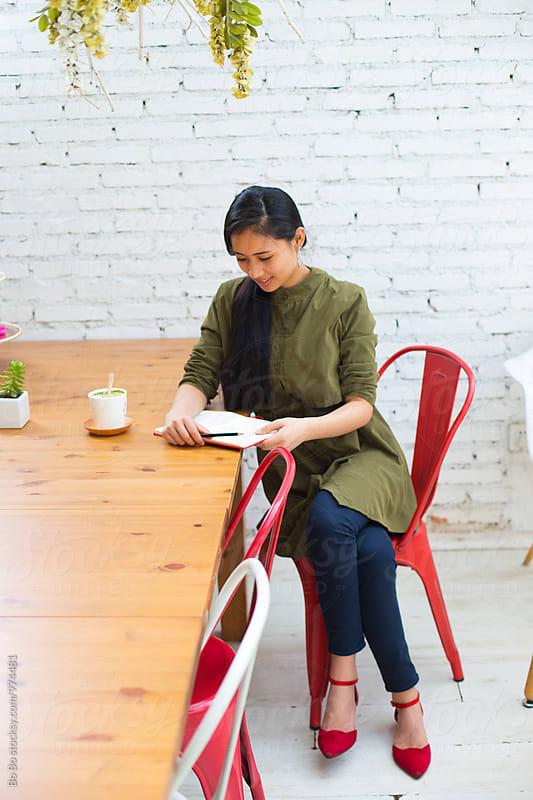 young asian businesswoman in office by Bo Bo for Stocksy United