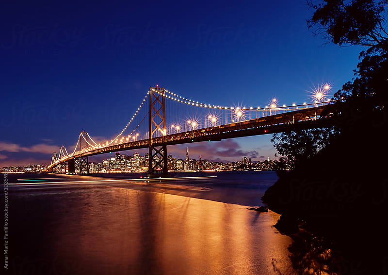 The San Francisco Bay Bridge lit up at night by Anna-Marie Panlilio for Stocksy United