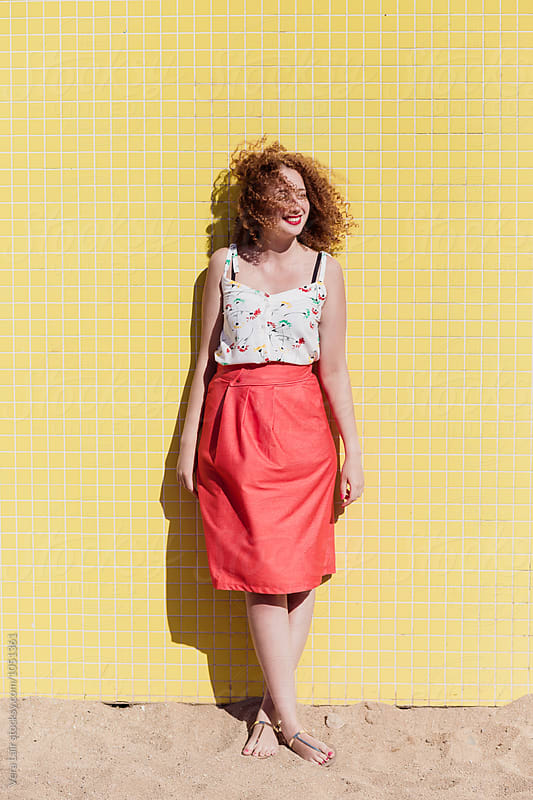 Young woman in front of a yellow wall by Vera Lair for Stocksy United
