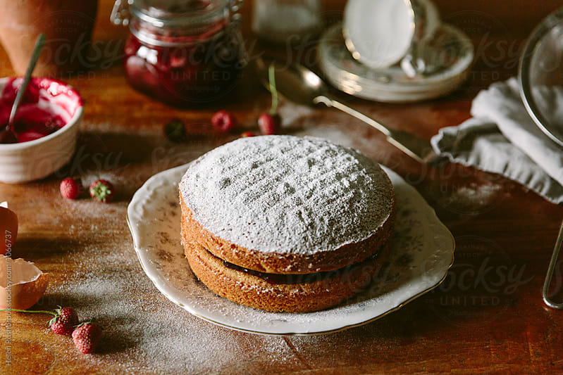 Sponge cake on a kitchen table. by Helen Rushbrook for Stocksy United
