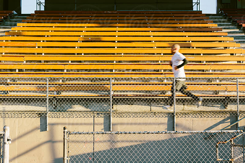Athletic Man Running Across Bleachers At Track And Field Stadium by Luke Mattson for Stocksy United