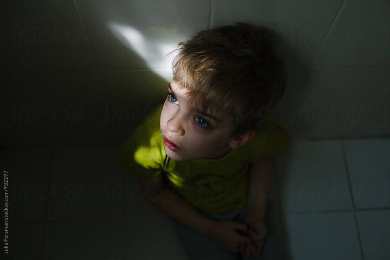 Boy sitting on bathroom floor with shaft of light on his face. by Julia Forsman for Stocksy United