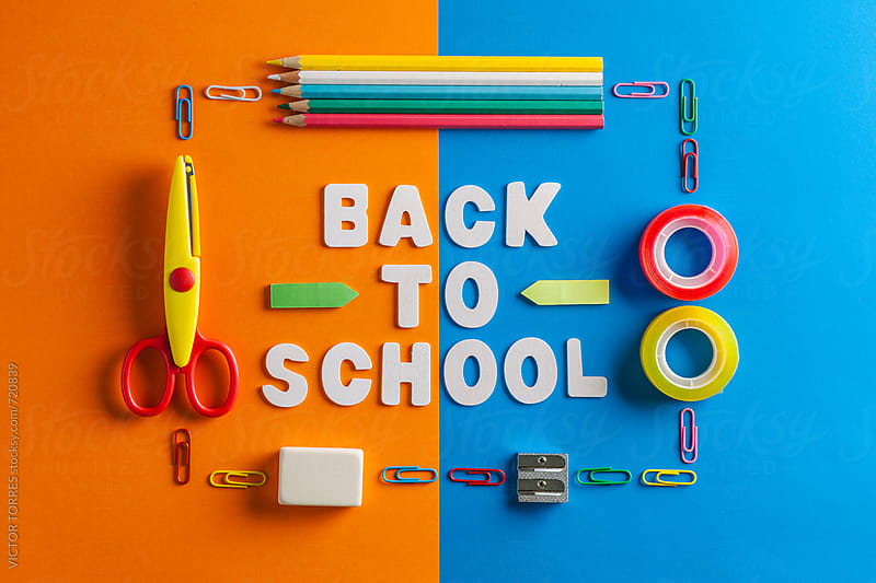 Schools supplies on a Blue and Orange Cardboards with Back to School Message by VICTOR TORRES for Stocksy United