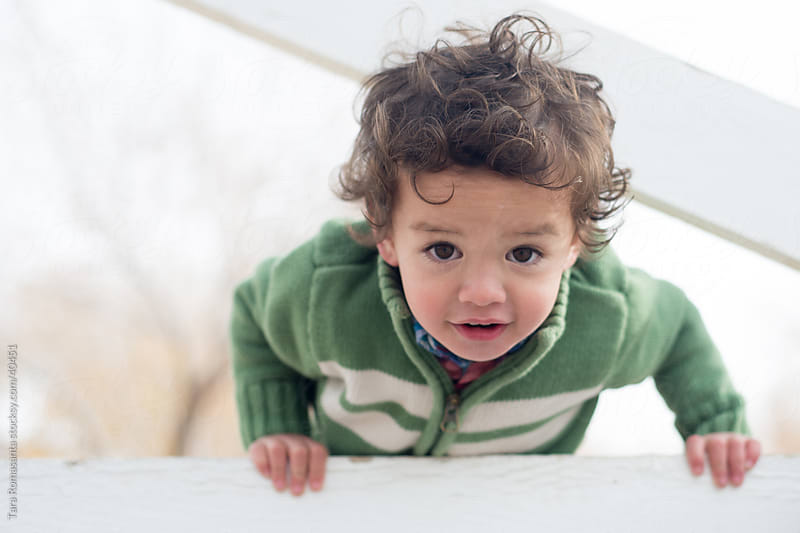 curly haired toddler plays peekaboo by Tara Romasanta for Stocksy United