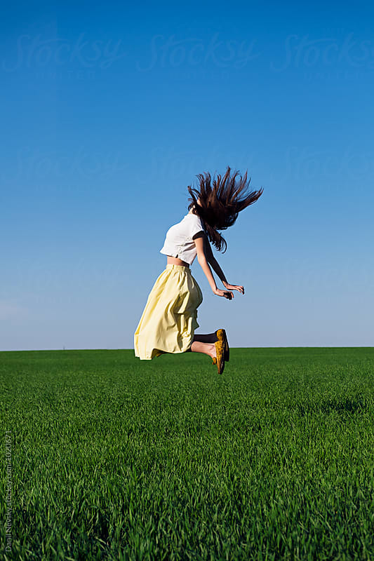 Side view of jumping brunette in field with blue sky by Danil Nevsky for Stocksy United