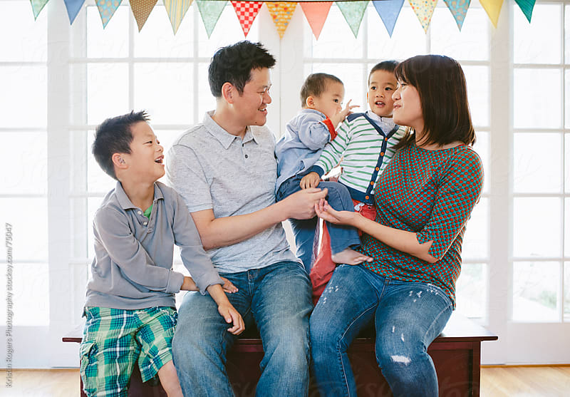 Family at home hugging and being silly  by Kristin Rogers Photography for Stocksy United