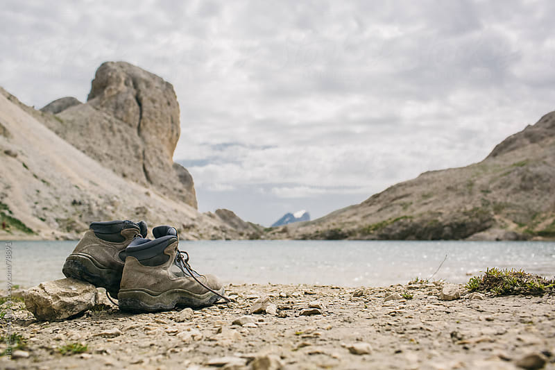 Boots of a hiker near a mountain lake by michela ravasio for Stocksy United
