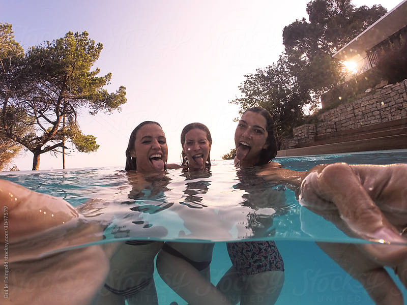 Young friends making selfie with go pro in pool by Guille Faingold for Stocksy United