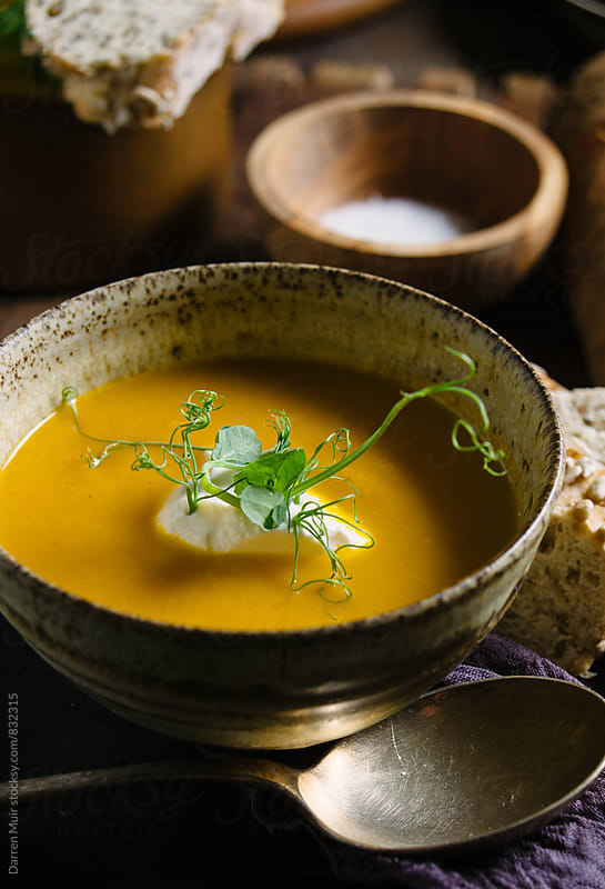 A bowl of carrot soup in a rustic setting. by Darren Muir for Stocksy United