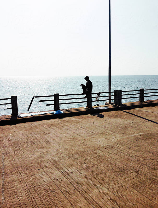 Lonely Man Sitting On Railing By The Ocean by VISUALSPECTRUM for Stocksy United