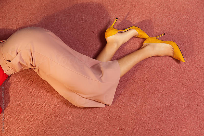 legs of a woman lying  down on the floor of a room by Ulaş and Merve for Stocksy United