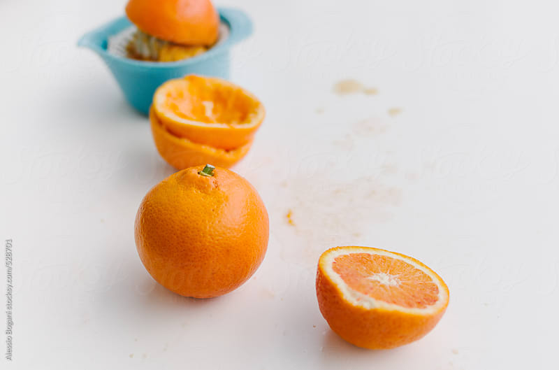 Oranges and juicer on plain background by Alessio Bogani for Stocksy United
