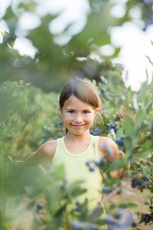 Smiling girl looking at camera through a row of blueberry bushes by Amanda Worrall for Stocksy United