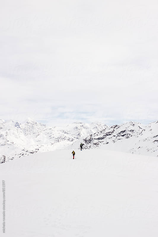 Men hiking on snow-covered mountains in winter by michela ravasio for Stocksy United