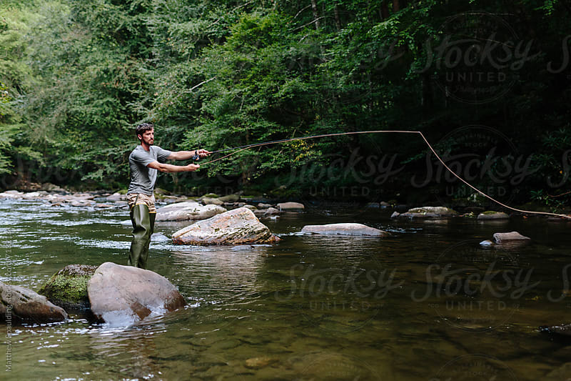 Man casting and fly-fishing in clear river trying to catch fish by Matthew Spaulding for Stocksy United