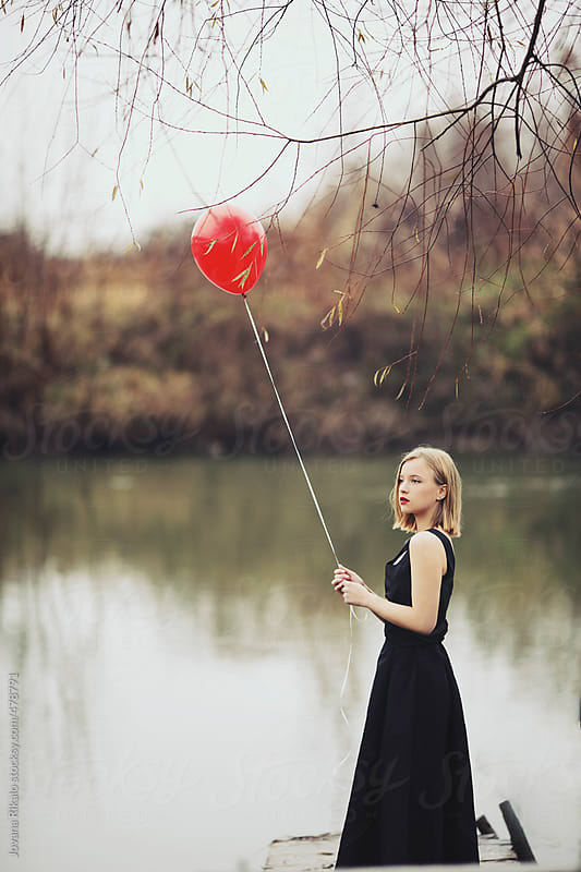 Young woman holding a red balloon by Jovana Rikalo for Stocksy United