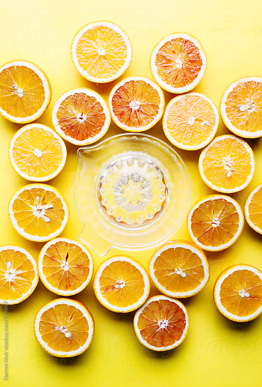 Oranges on a yellow background. Half oranges and a juicer on a yellow background. by Darren Muir for Stocksy United