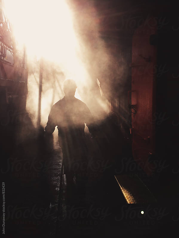 Walking through the smoke by John Dunaway for Stocksy United