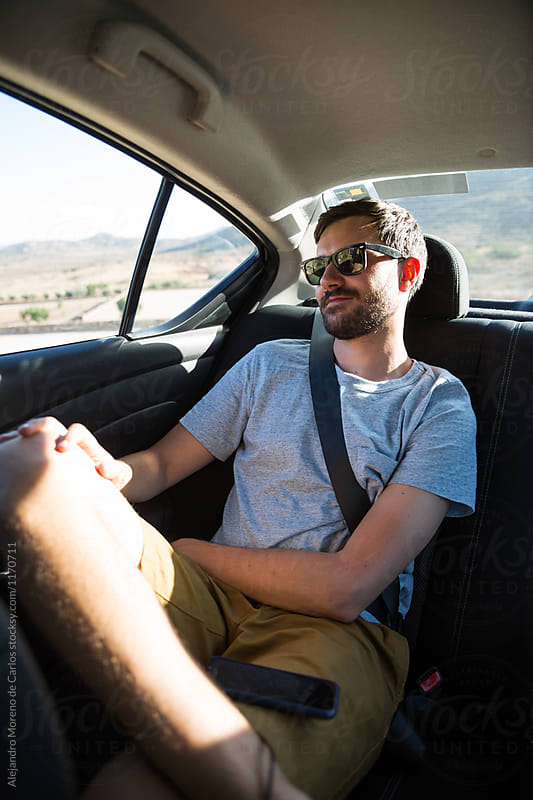 Young man traveling on the back of a car on a road trip at sunset