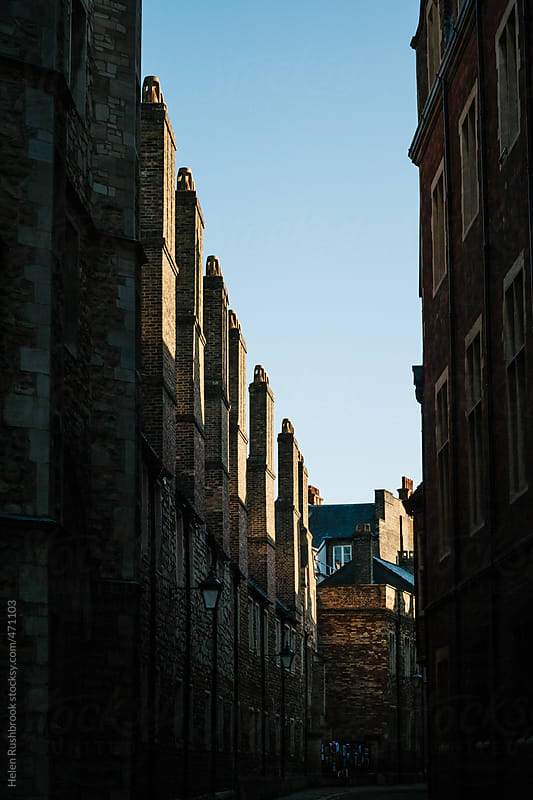 Tall chimneys and blue sky - a shadowy street lined by tall, old. buildings. by Helen Rushbrook for Stocksy United