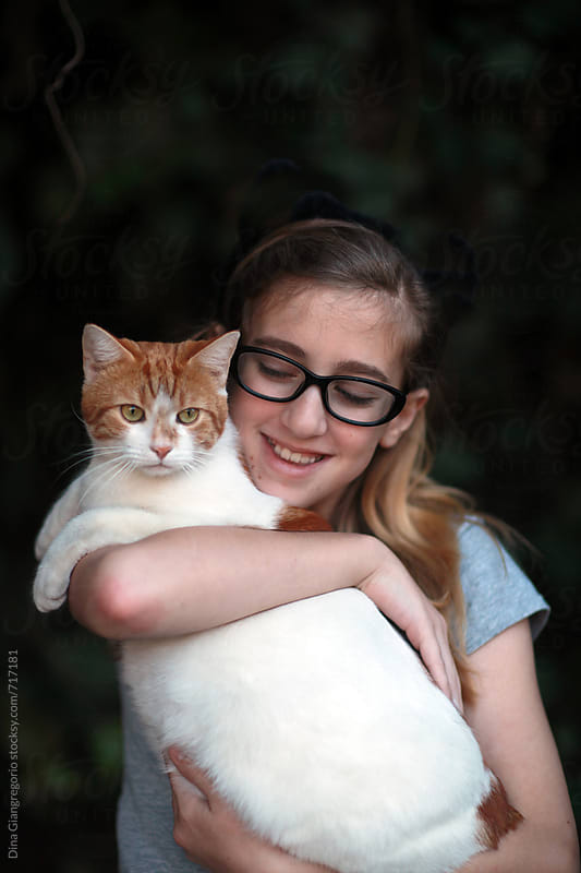 Young Girl Wearing Glasses Holding Orange and White Cat by Dina Giangregorio for Stocksy United