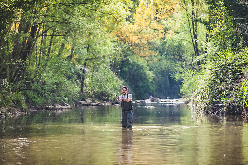 Young Man Fishing in a Small River by Giorgio Magini for Stocksy United
