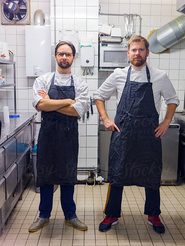 Two professional chefs or cooks standing in a small kitchen by Ivo de Bruijn for Stocksy United