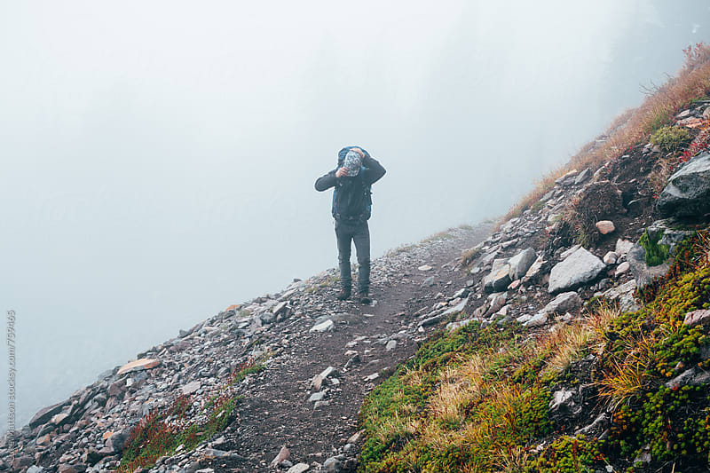 Young Male Backpacker Adjusting Cap On Mountain Trail by Luke Mattson for Stocksy United