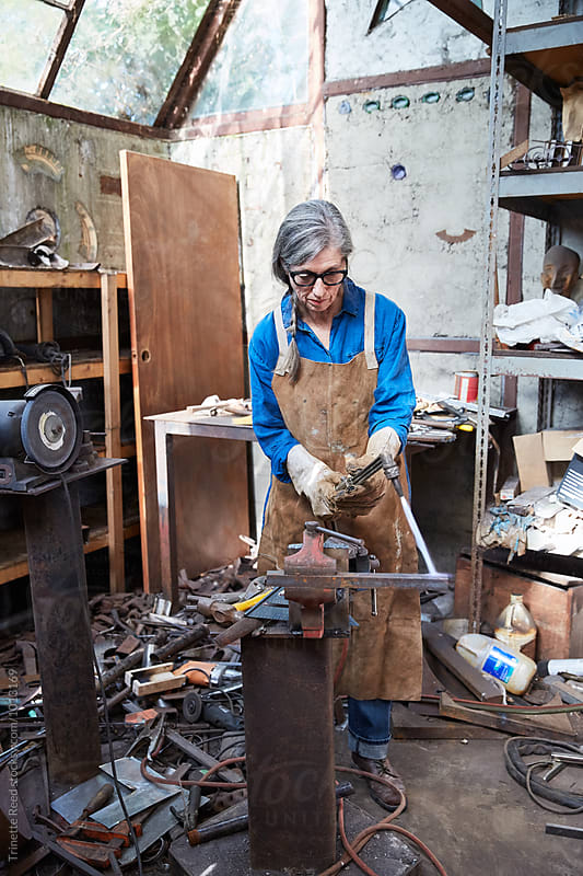 Portrait of senior woman inside her metal shop by Trinette Reed for Stocksy United