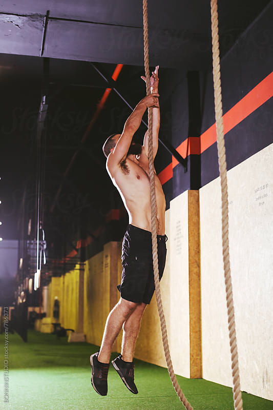 Man climbing a rope in a gym box. by BONNINSTUDIO for Stocksy United