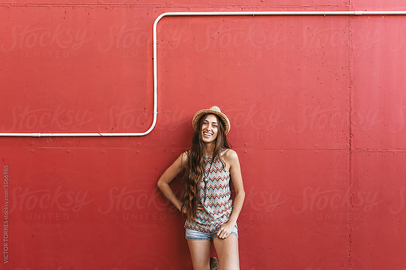 Portrait of a Beautiful Teenager over a Red Background by Victor Torres for Stocksy United
