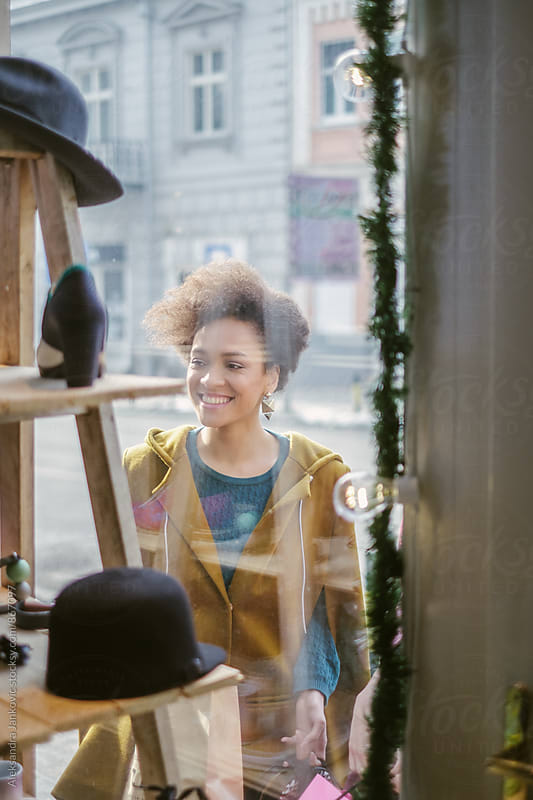 Young Woman Looking at the Goods Displayed in Shop Window by Aleksandra Jankovic for Stocksy United